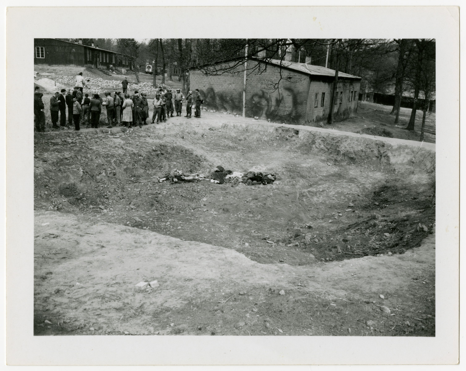 Corpses lie in a sunken mass grave outside a barrack of the Langenstein-Zwieberge concentration camp while survivors gather nearby.