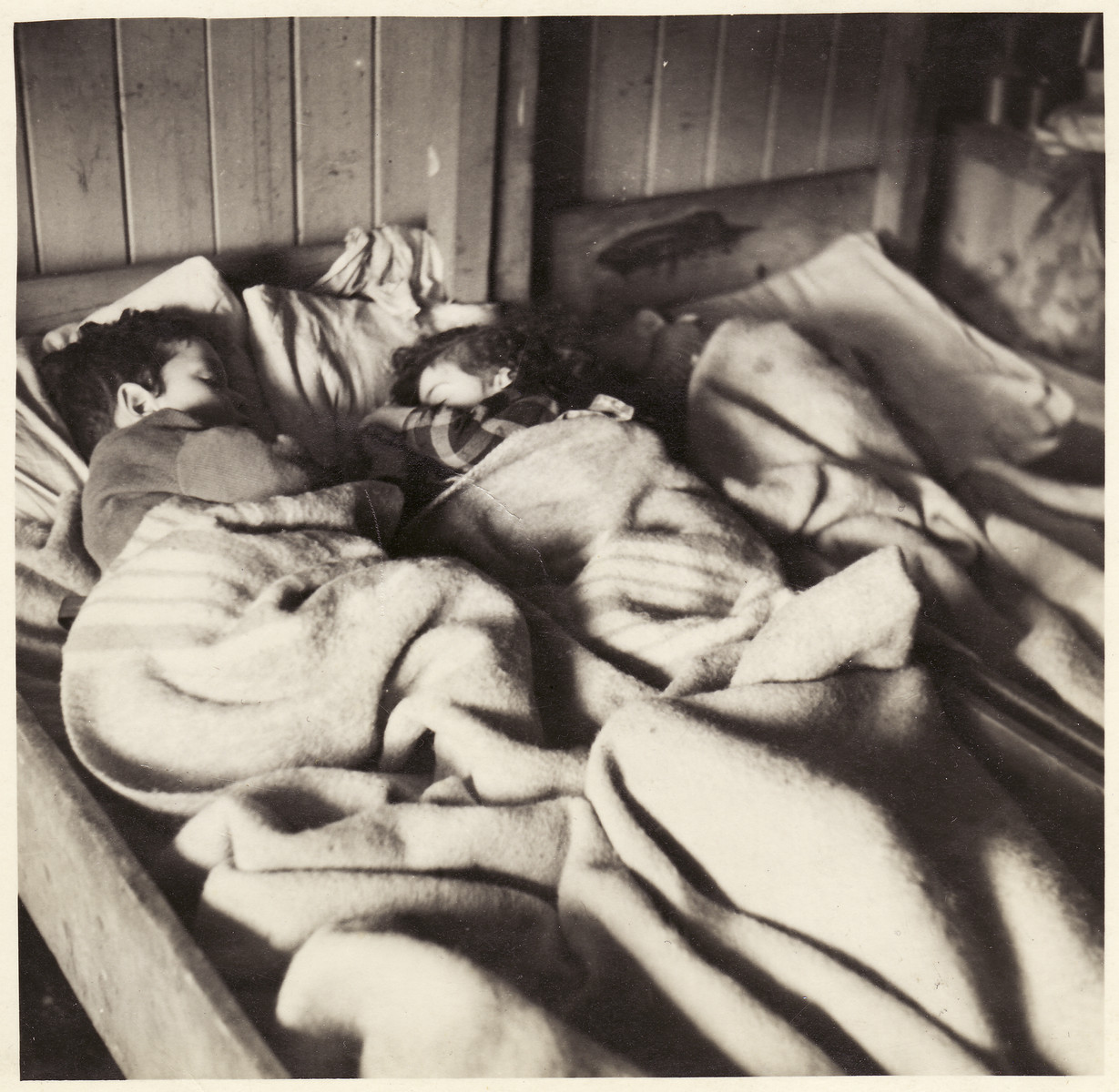 Young children sleep under a blanket in Bergen Belsen.  [This photo might have been taken after the camp was converted to a DP camp.]