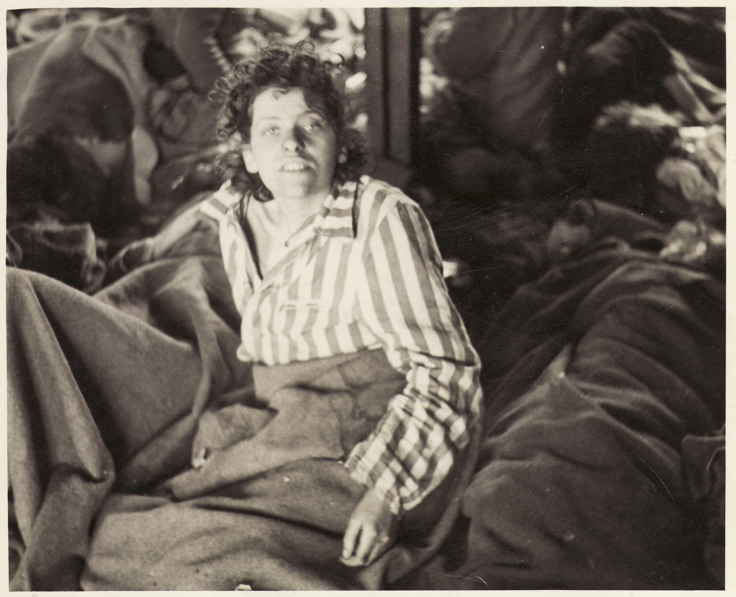 A female survivor and other women lie, covered in blankets, on the floor of a barracks in Bergen-Belsen concentration camp after liberation.