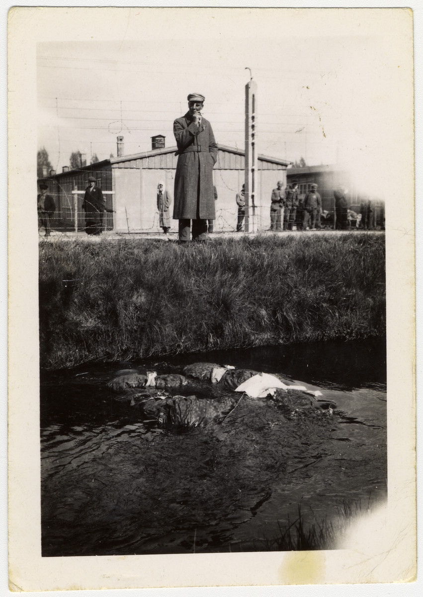 A survivor stands next to the Dachau moat and looks down on the corpses of killed SS men floating in it.