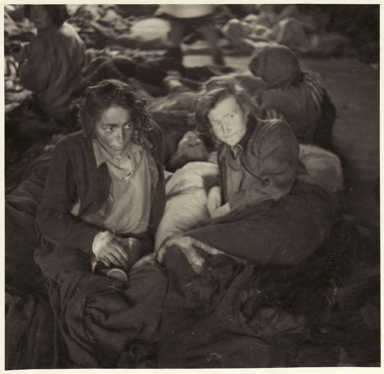 Female survivors lie, covered in blankets, on the floor of a barracks in the Bergen-Belsen concentration camp.