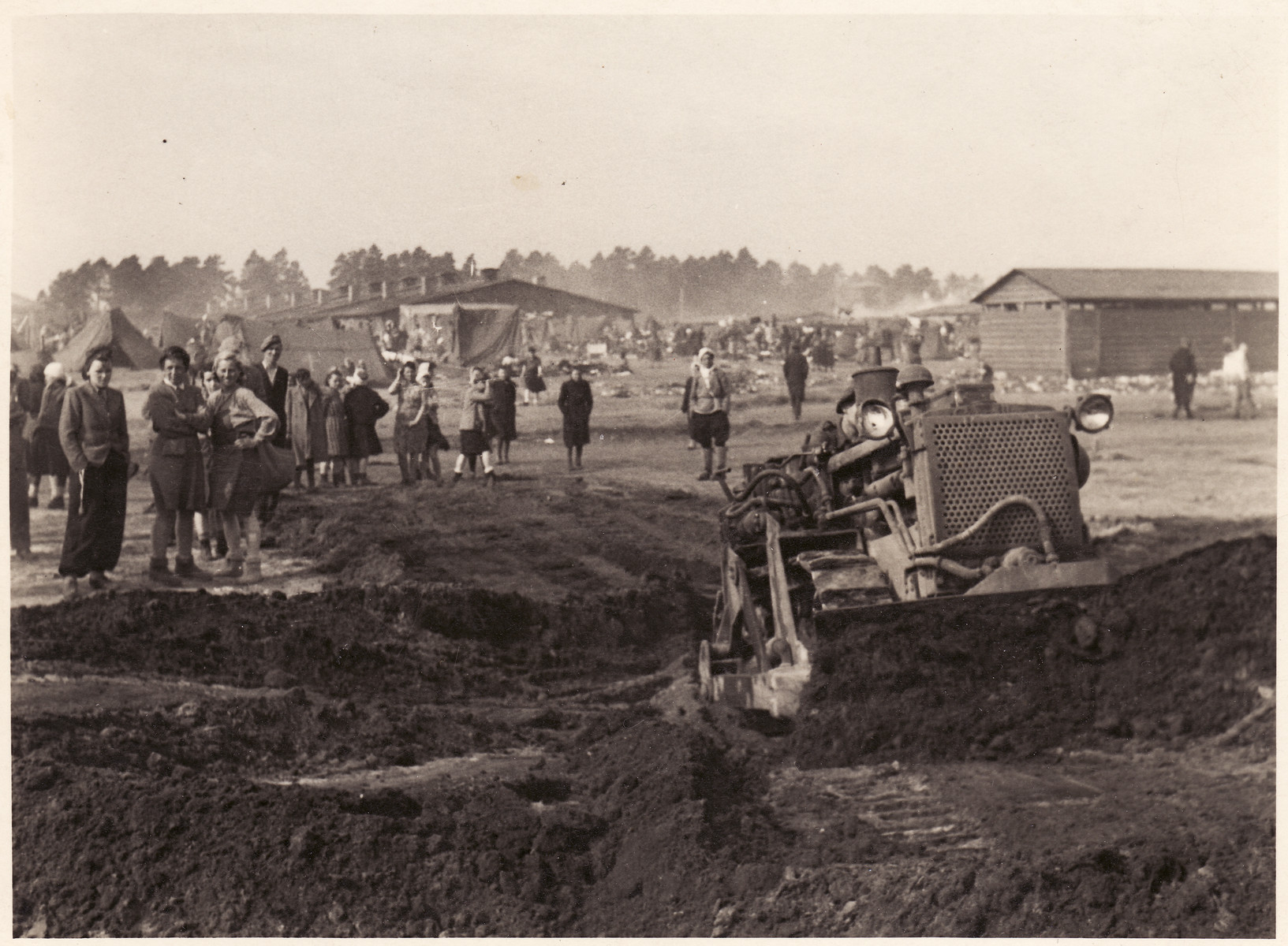 Survivors stand and watch as a tractor digs a mass grave at the Bergen-Belsen concentration camp.