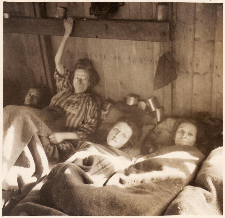 Female survivors lie in bunks inside the barracks of the Bergen-Belsen concentration camp.