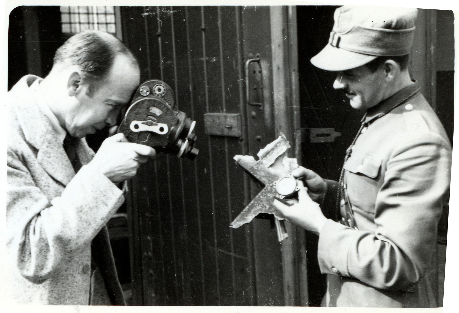 Julien Bryan films objects [possibly the wreckage from a German plane] in a Polish soldier's hand in besieged Warsaw.