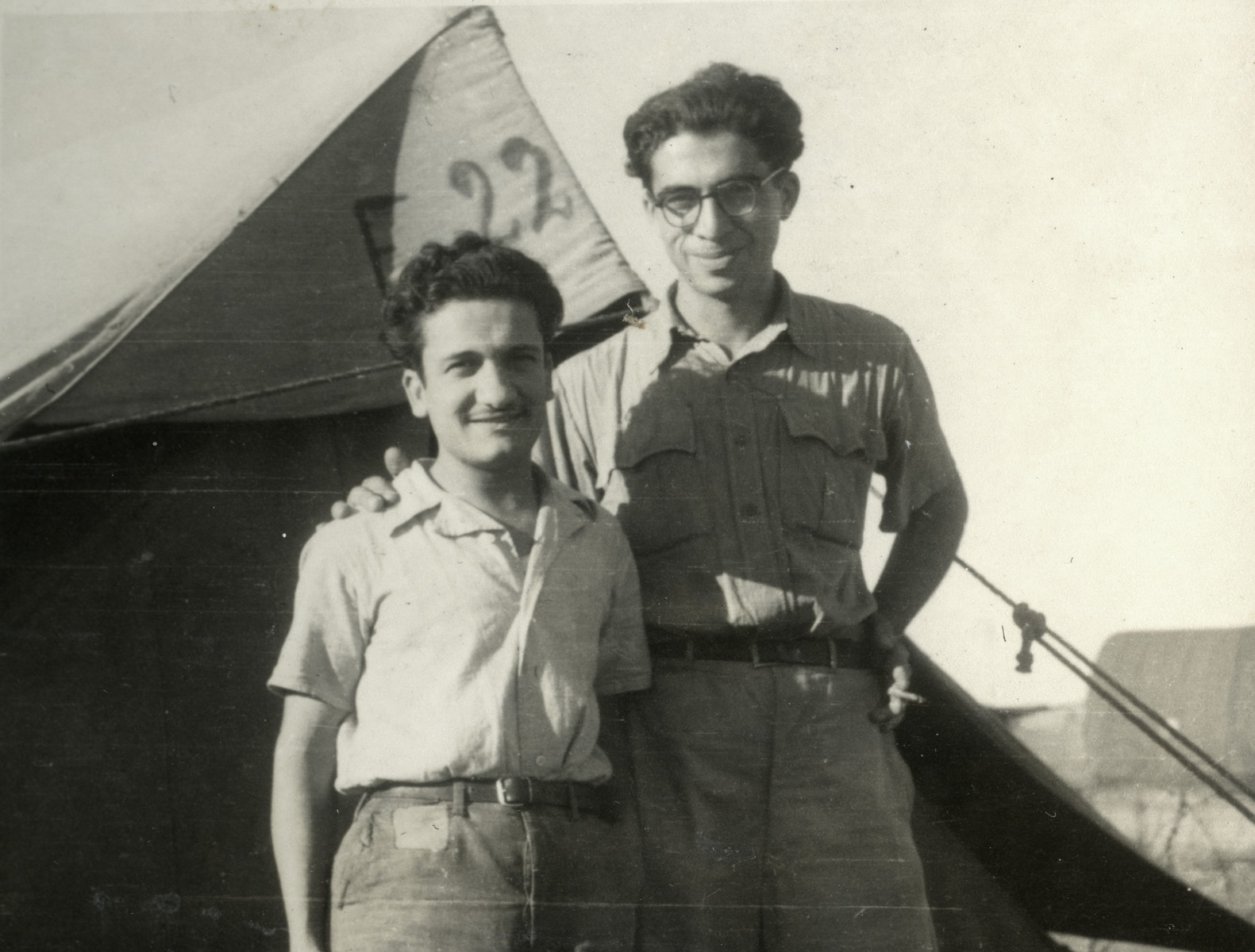 Dario Navarra and Giacomo Mattarazzi pose in front of a tent in a Cyprus refugee camp.