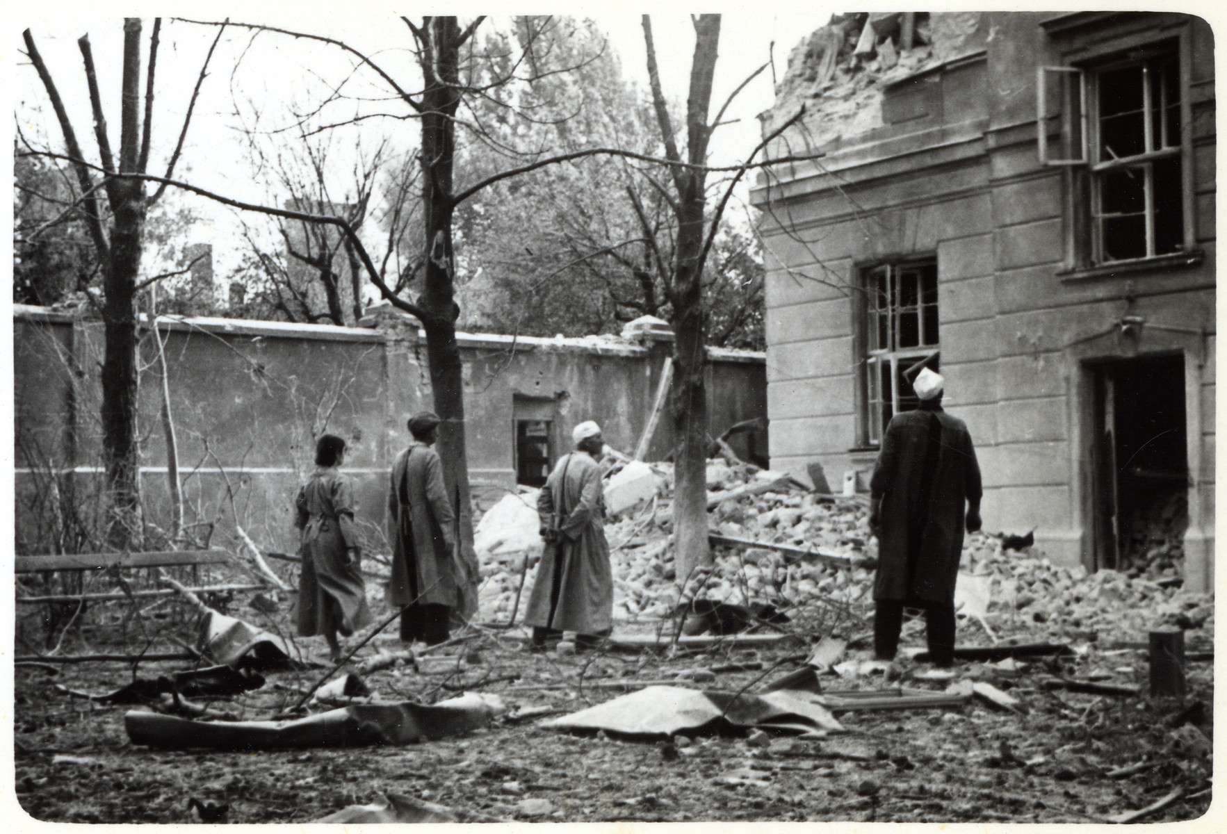 Polish doctors and nurses look at the damage to their hospital, The Transfiguration of the Lord, following its bombing during the siege of Warsaw.