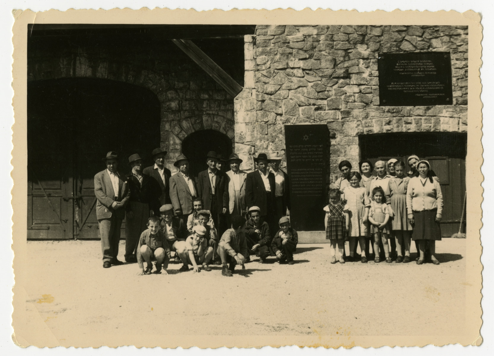 A group of Orthodox Jewish Holocaust survivors and their children visit the Mauthausen concentration camp.  They had fled to Austria from Hungary after the 1956 revolution and were living in Asten, Austria, which is between Linz and Mauthausen.