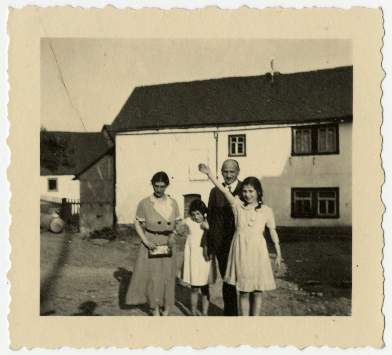 The Loeb family stands outside a warehouse in Halsenbach, Germany.  From left to right are Caroline, Hildegarde, Rudolf and Clare Loeb.