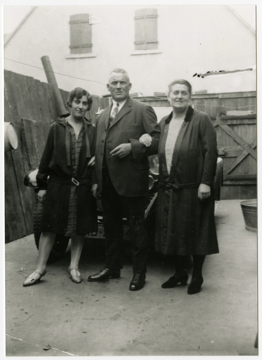 Johanna and Heinrich Baehr pose along with their daughter, Ida Baehr Lang, in front of an automobile.