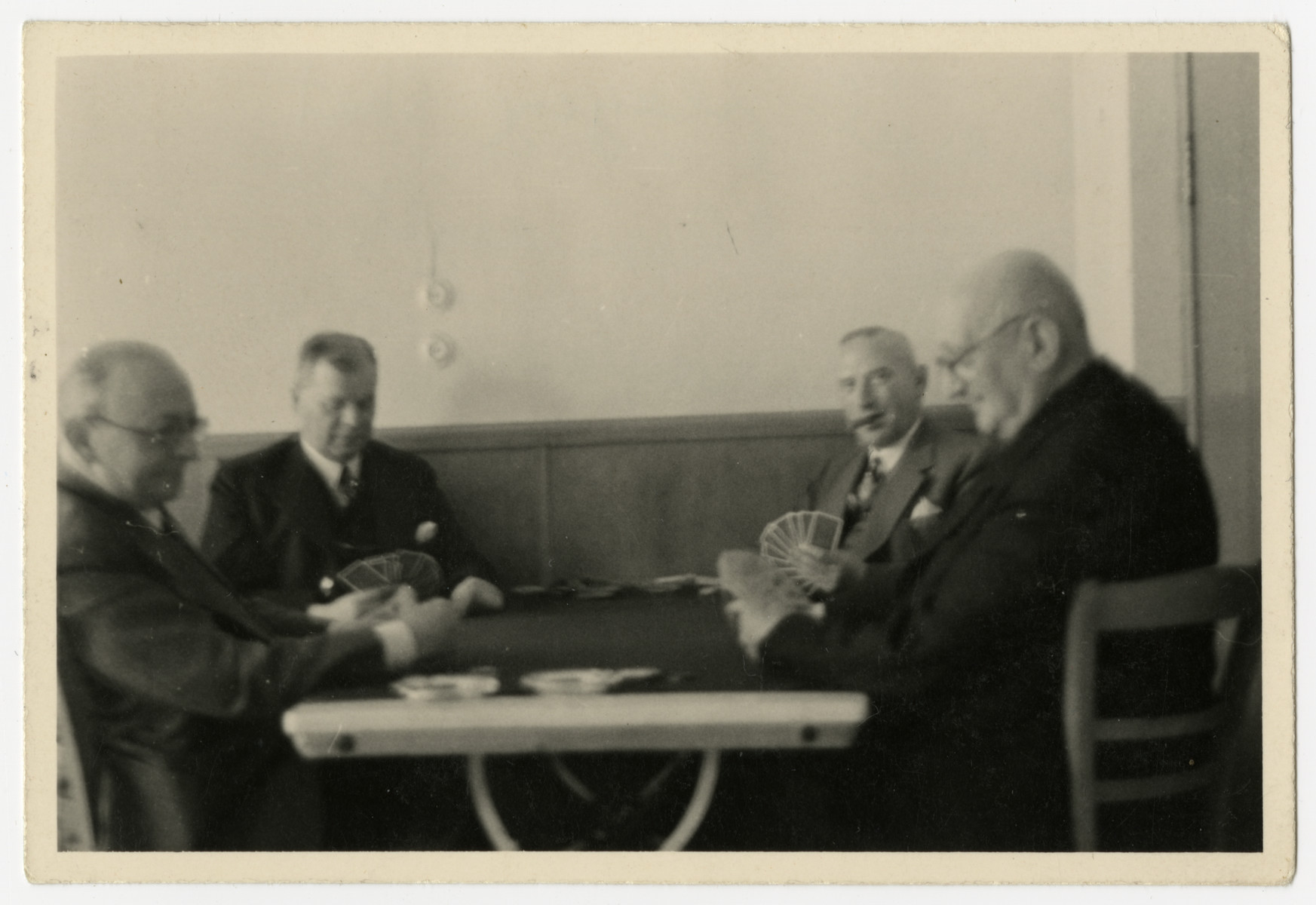 A group of men play a game of cards.  Emil Gundelfinger is second from the right, smoking a cigar.