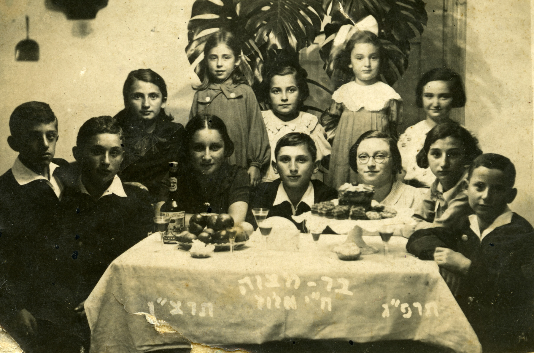 Children gather around a table to celebrate the bar mitzvah of Lonek (Leon) Halberstadt in Krasnik Poland.  He is sitting in the center, and his sister Jazda Halberstadt is to his left.  Regina Fryd is standing behind him and Jadza Styck is standing on the right.