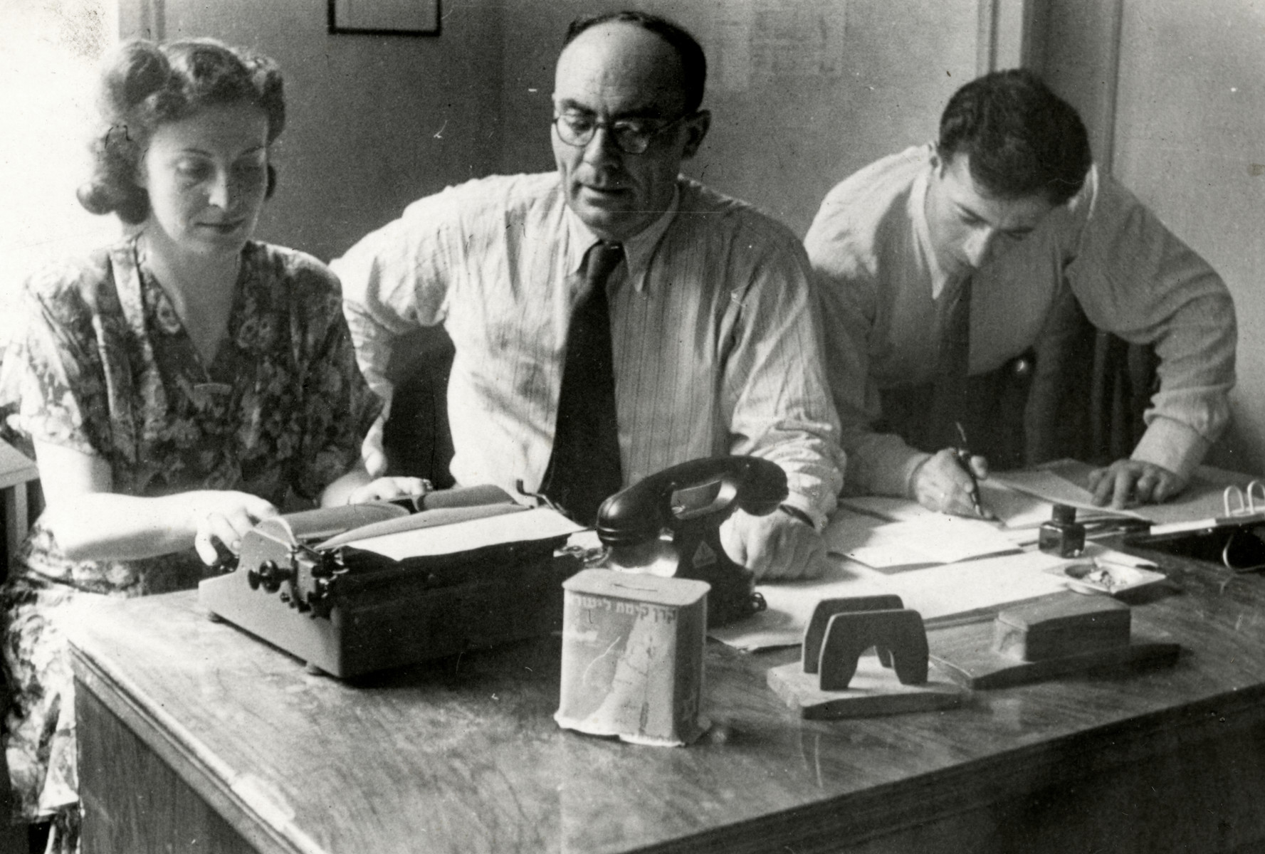 Three people work in the office of the Jewish Agency for Palestine in the Stuttgart displaced persons' camp.  Pictured typing on the left is Yocheved Fryd.