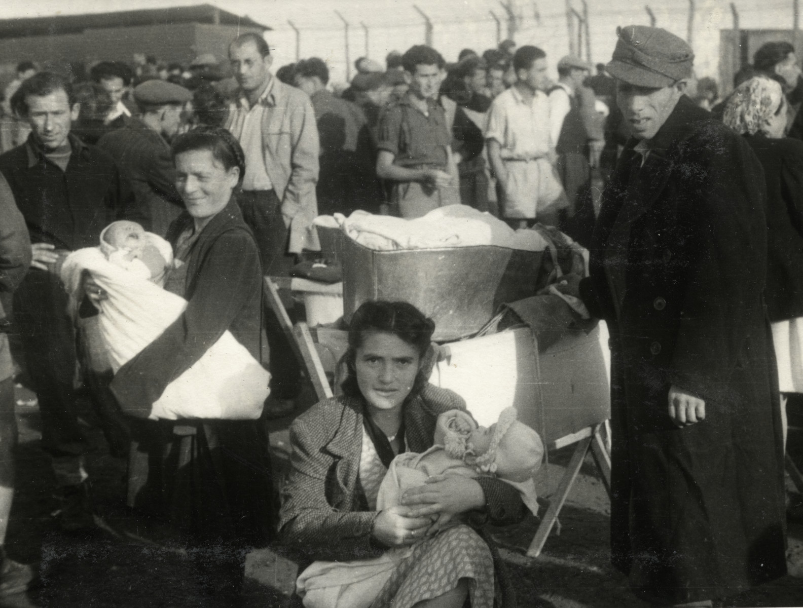 Refugees in a camp in Cyprus, some mothers carrying newborn babies, crowd behind the barbed wire fence.