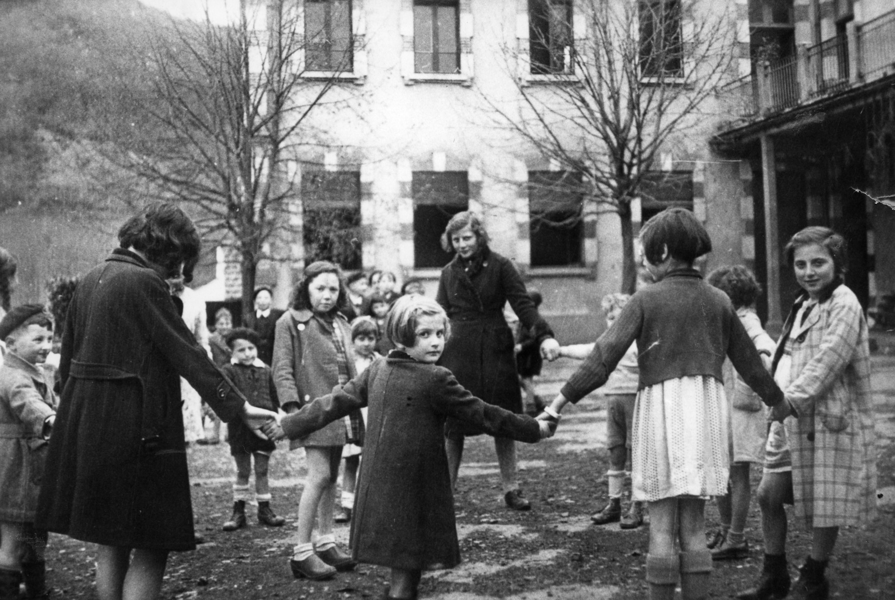 A group of children hold hands during an outside game at Aspet.