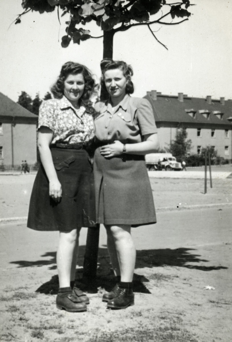 Two young women pose in front of a tree in the Bergen Belsen displaced persons camp.   Pictured are Lili Deutsch on the right with her friend, Goldy.