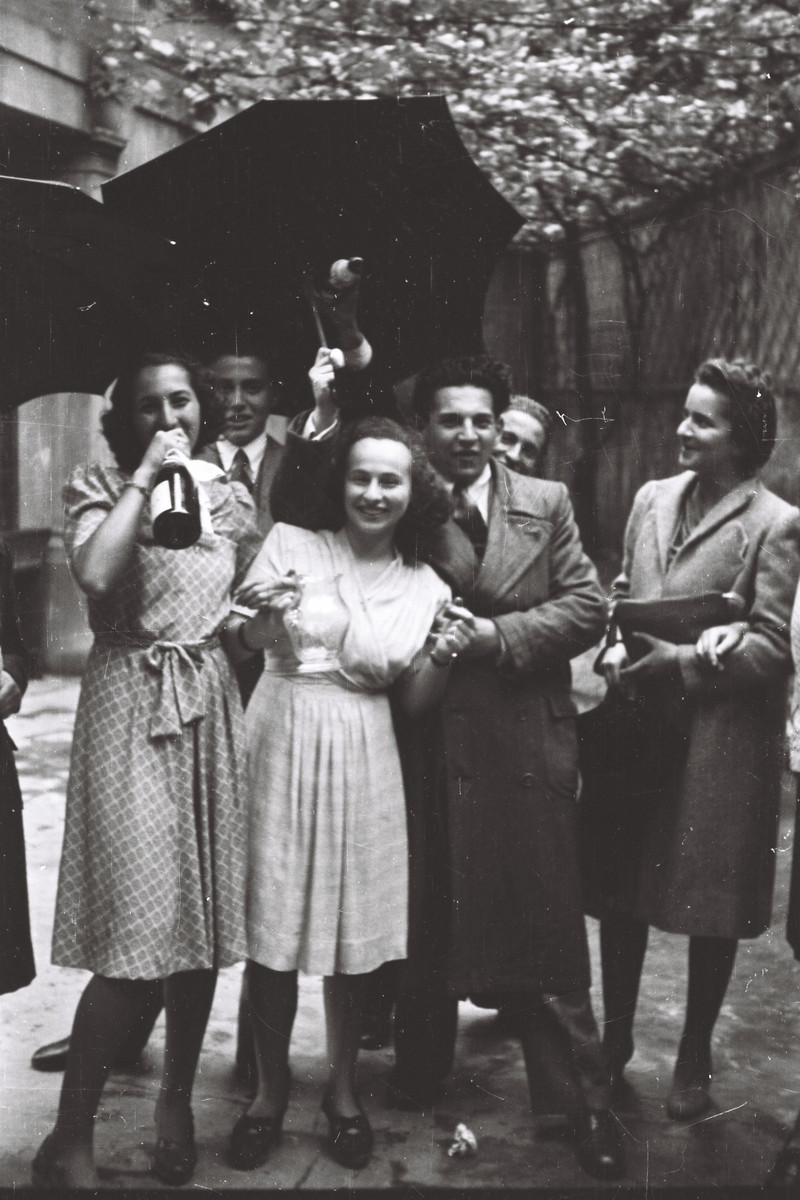 Students from the Scuolo via Eupili, pose together with a wine bottle under an umbrella.  Pictured are Emma Pontremon, Anna Marcello Falco, Etto Nachamuli, and Constanza D'Anconia.