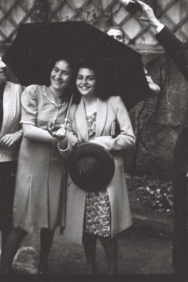 Lia Foa and Luciana Vitale, two students in tje Scuolo via Eupili, huddle together under an umbrella.