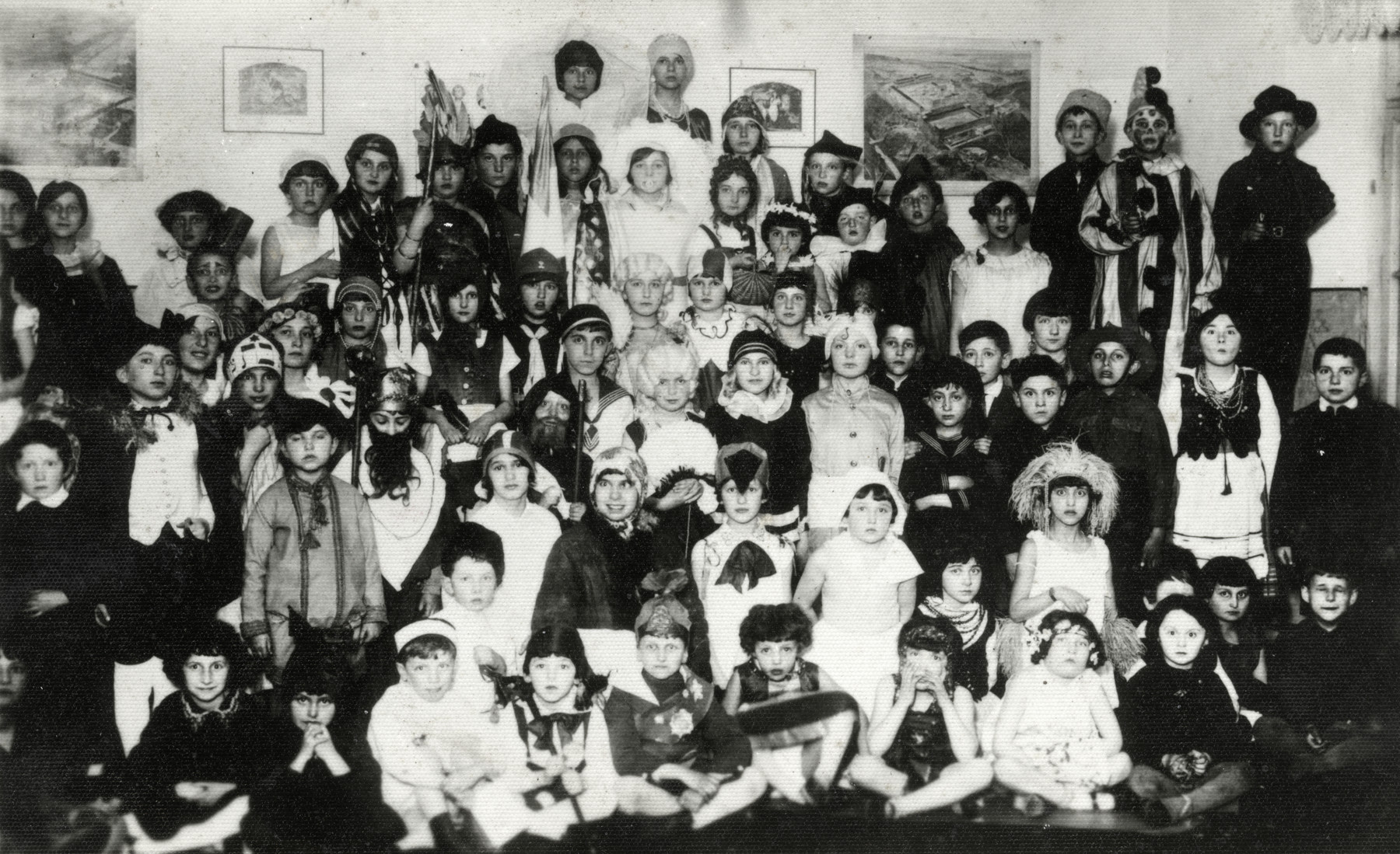 Children in the Humanistic school in Lublin, Poland pose for a group portrait in their Purim costumes.  Among those pictured is Yocheved Fryd dressed as Rebecca in a head scarf.