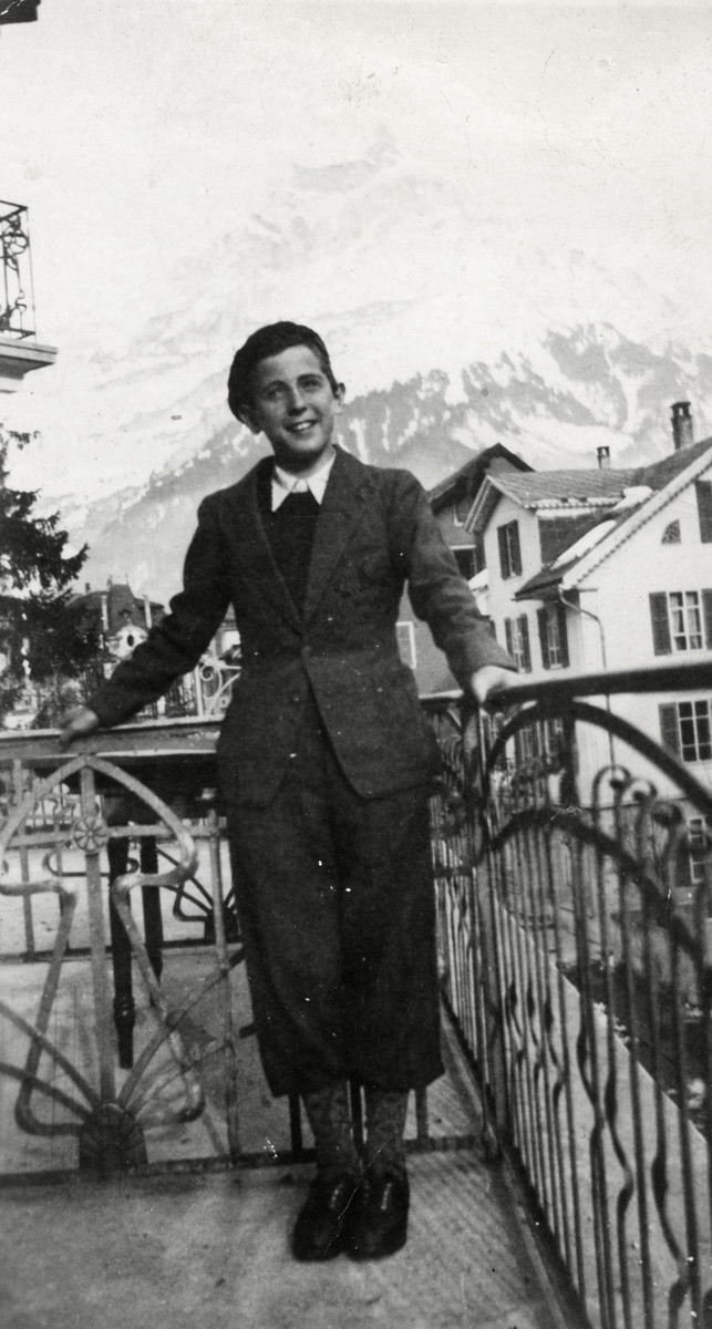 Heinz Mayer stands on the porch of the Orthodox Zionist children's home in Engelberg, Switzerland in front of a view of the Alps.