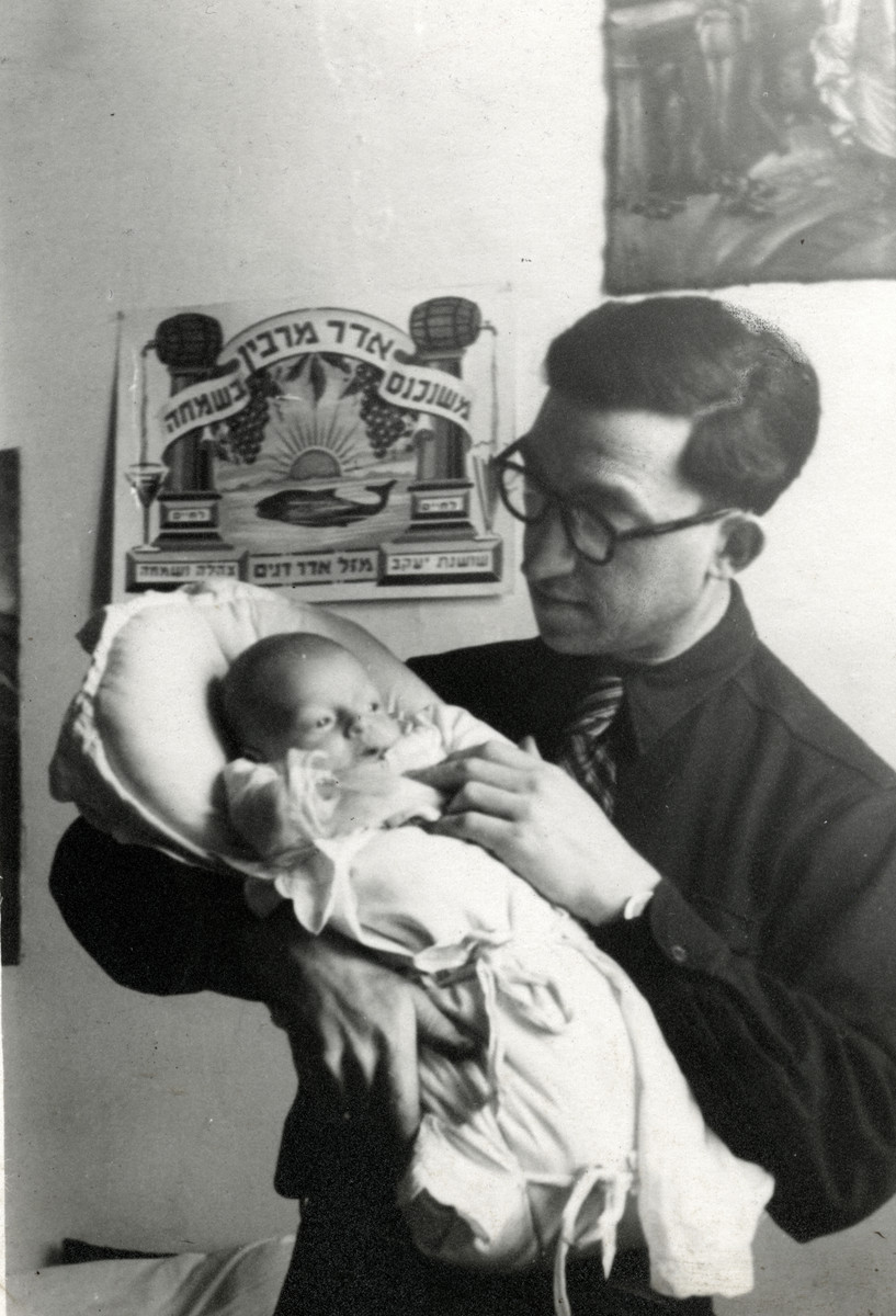 """Zvi Silberman holds his newborn son in a displaced persons' camp in Austria.  Behind them is a sign that reads in Hebrew, """"when Adar [the Hebrew month of Purim] comes happiness is multiplied."""""""