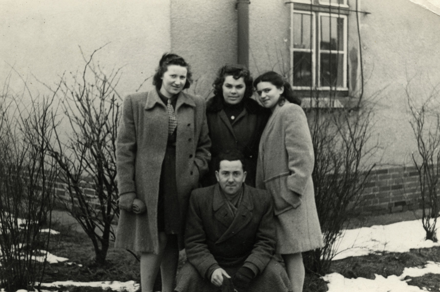Friends pose in front of a building in the Bergen-Belsen displaced persons' camp.   Pictured are Lili Deutsch (top left) wearing a coat made from a blanket, her sister Esther, and friend Leib (bottom).