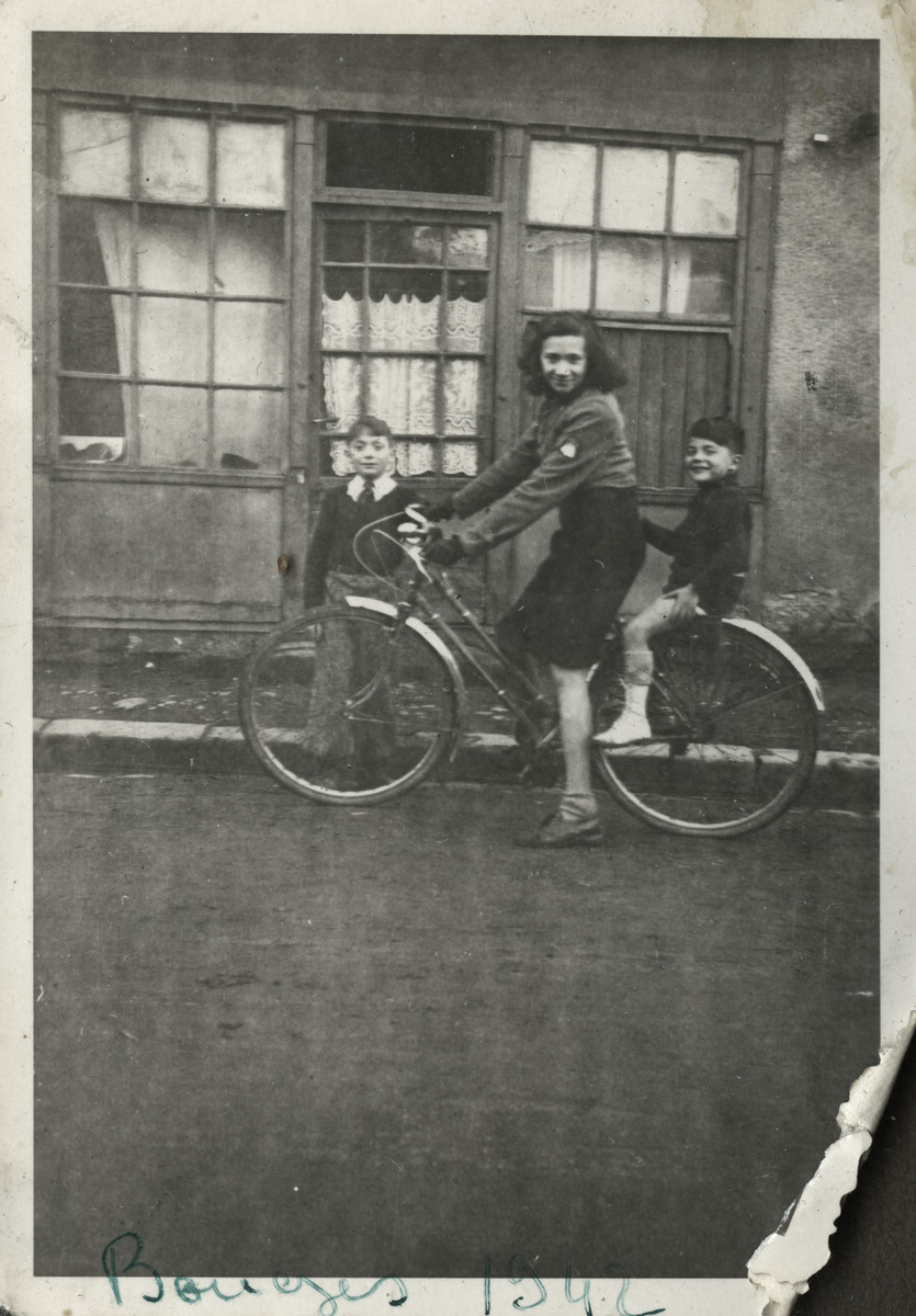 Annie rides a bicycle with her brother Robert on the back.  Max is standing on the left.