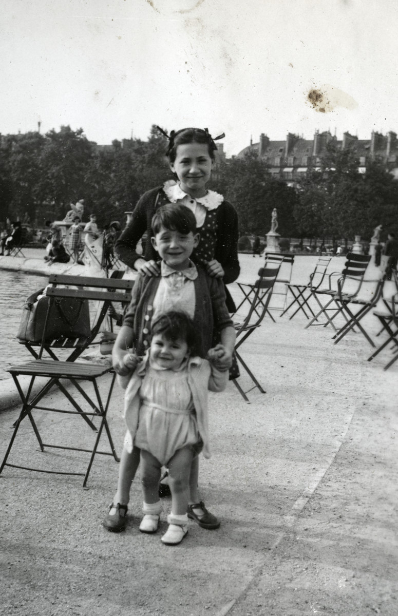 The Spira children stand in a row in a plaza in Paris.  From front to back are Robert, Max and Annie Spira.