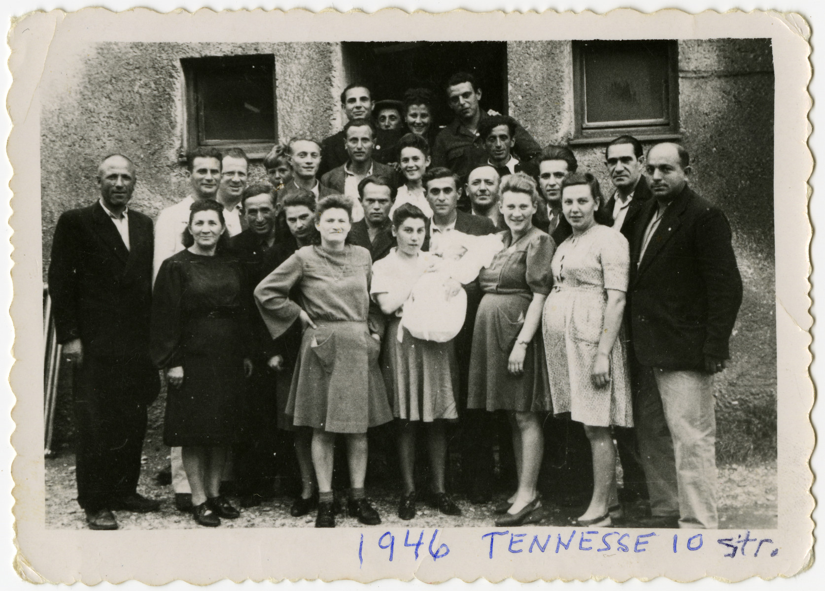 A large group of men and women, including several pregnant women and one holding an infant, pose outside 10 Tennesse Street in the Foehrenwald displaced person's camp.  Leon and Sally Korn are pictured in the third row in the center.