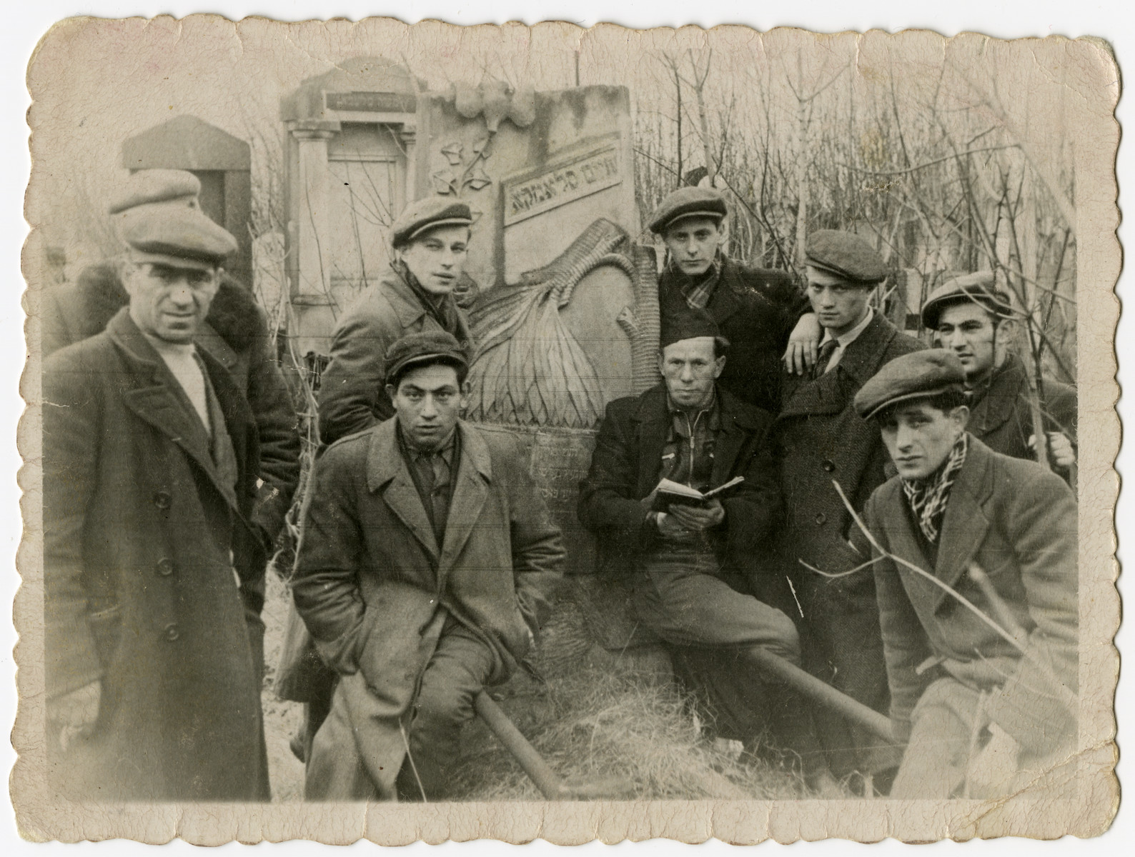 Jewish survivors pray in the desecrated Jewish cemetery near Lublin.  Leon Korn is standing in the back second to the right.