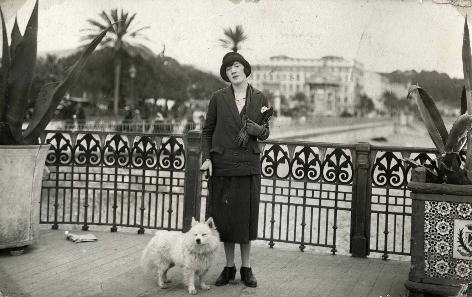 Camille Spira poses on a street in Vichy with a dog.