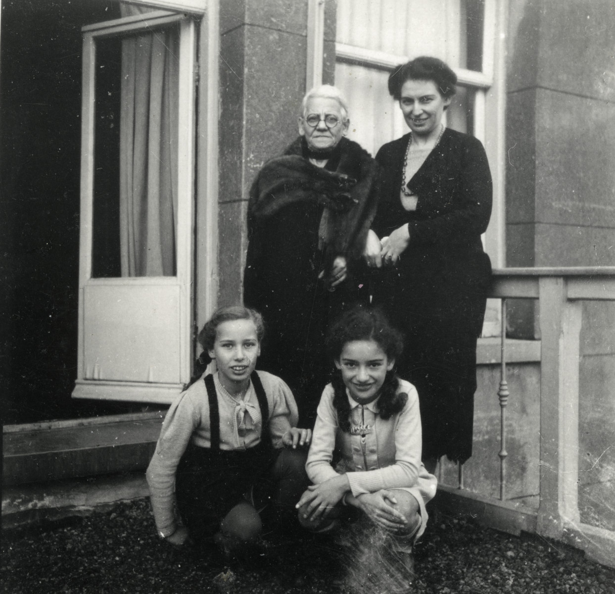Prewar photograph of the women of the van Collem family standing outside their apartment.  Pictured are Marta and Ilse van Collem, their mother Lotte and grandmother.