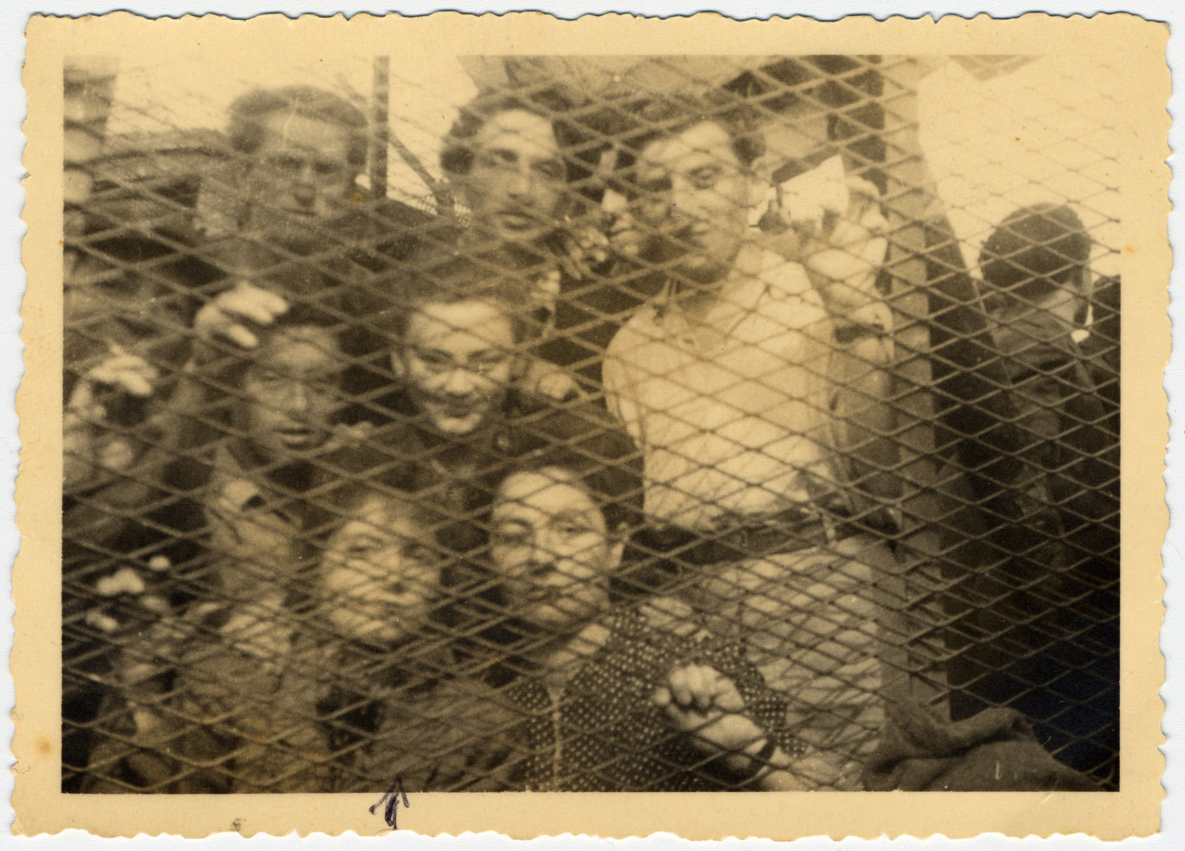 A group of passengers from the Exodus peers out behind a wire fence [probably in Haifa harbor].  Among those pictured is Rachel Krygier.