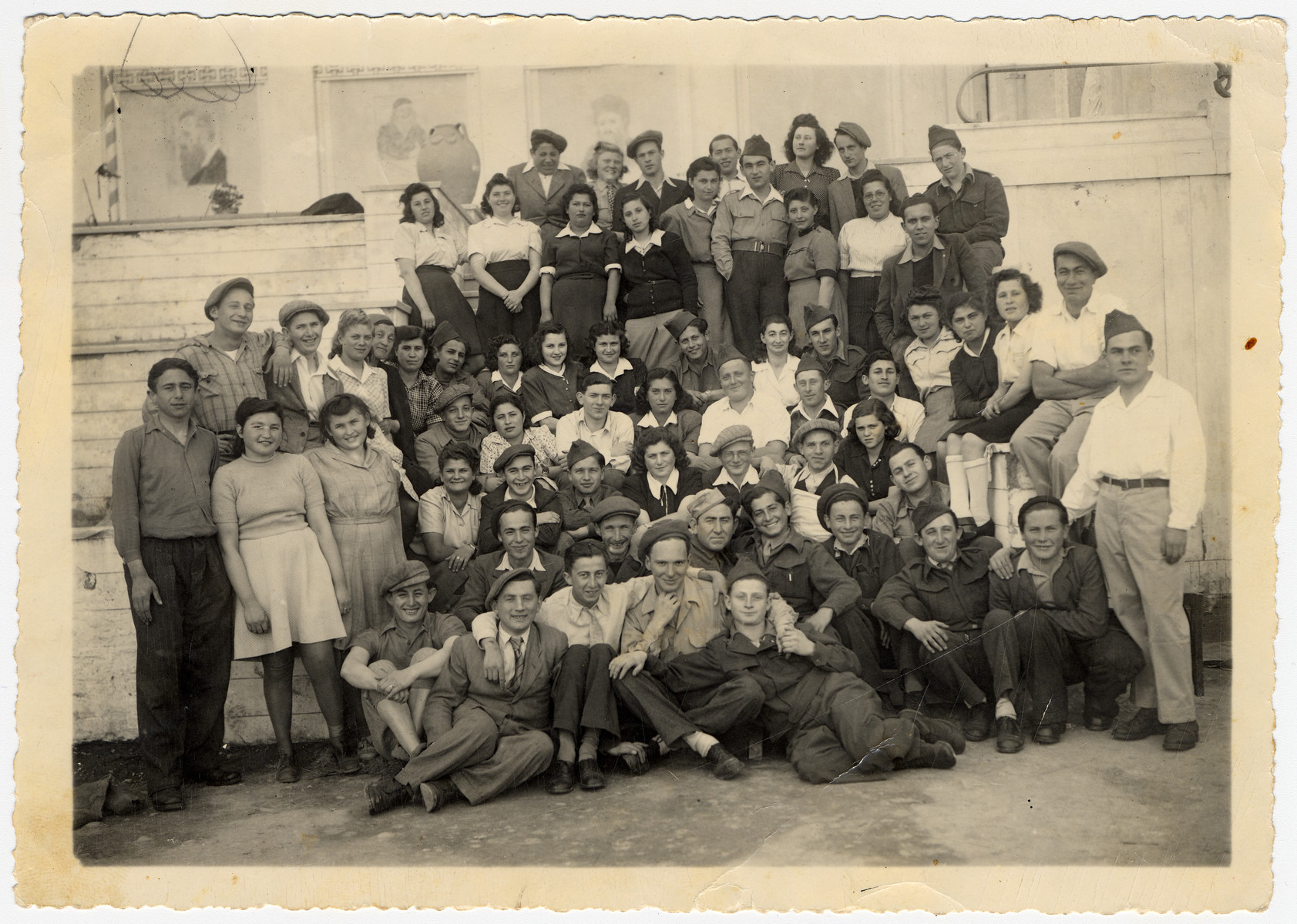 Group portrait of displaced persons in Kibbutz Mekor Baruch, a Poal Mizrachi fishing hachshara in Bacoli, Italy.  Among those pictured are David Hirshkoviz, Yomi Feld, Meir Shtasel, Mordechai Feldman, Reuven Yoto, Chaya Weiss, Tzipora Weiss, Ben Zion Gasner,and Moshe Berger.