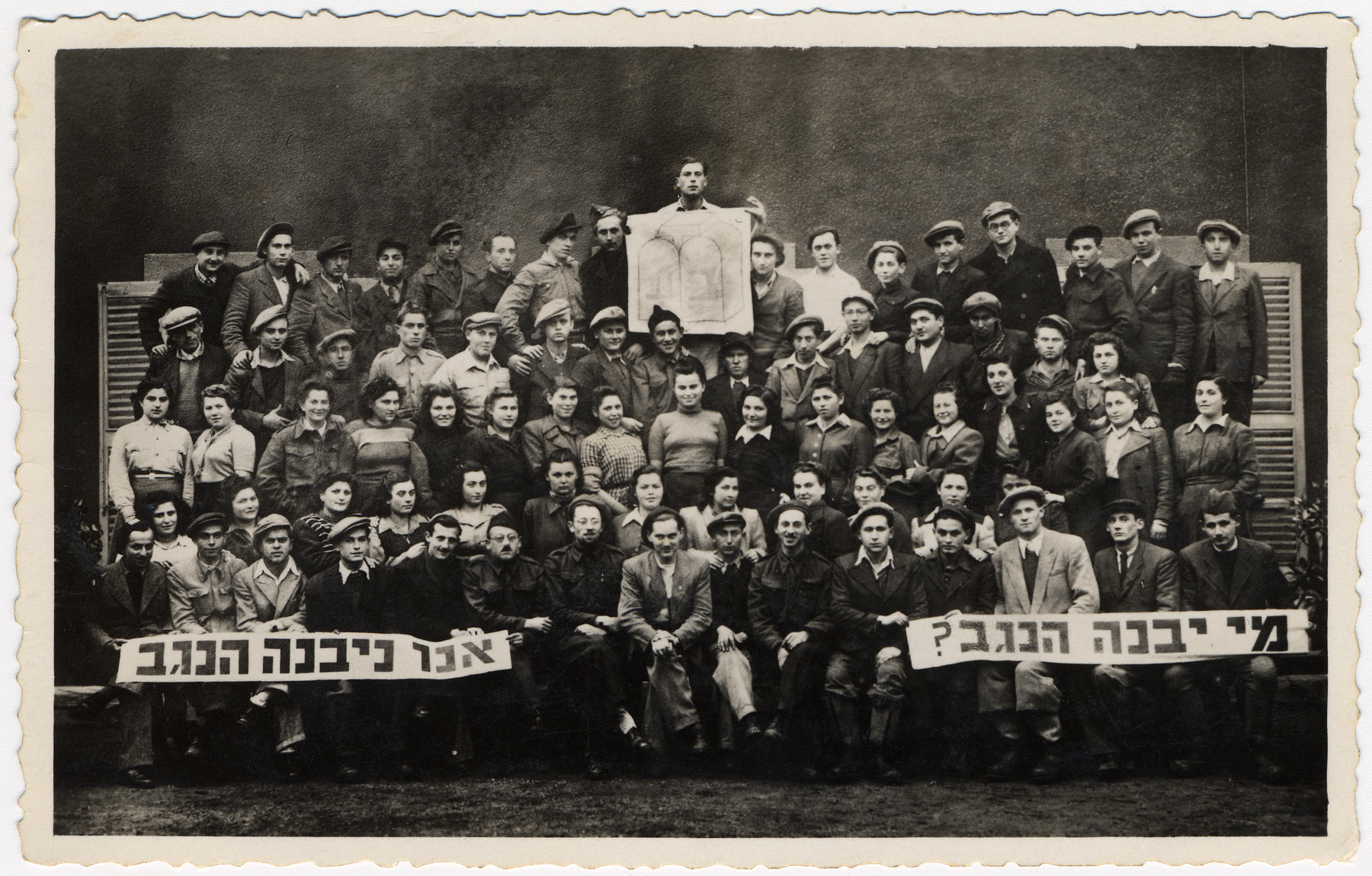 "Group portrait of members of a Poal Mizrachi hachshara.  They are holding a sign with the Bnai Akiva logo and Hebrew banners which read ""Who will build the Negev?  We will build the Negev""."