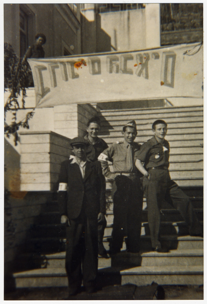 Four Jewish displaced persons stand on outdoor steps underneath a welcome banner in Kibbutz Mekor Baruch, a Poal Mizrachi fishing hachshara in Bacoli, Italy.