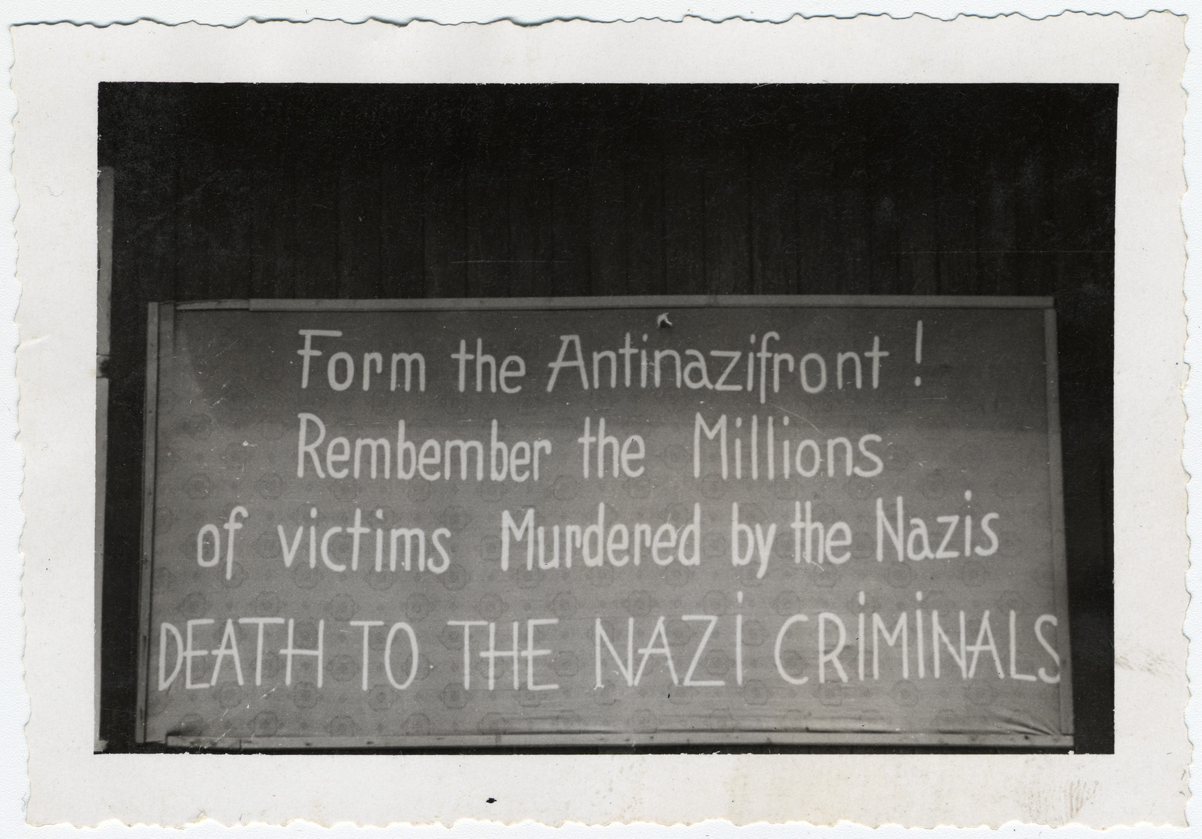 "A sign posted [probably in Buchenwald] that says, ""Form the Antinazifront! Remember the Millions of victims Murdered by the Nazis/ DEATH TO THE NAZI CRIMINALS."""