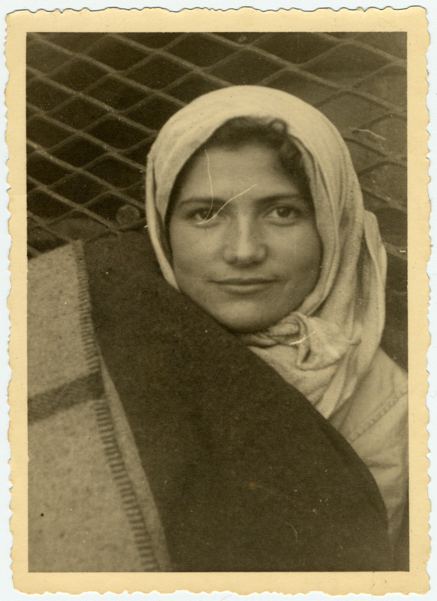 Rachel Krygier, a passenger on the ship the Exodus, peers out behind a blanket [probably in Haifa harbor].