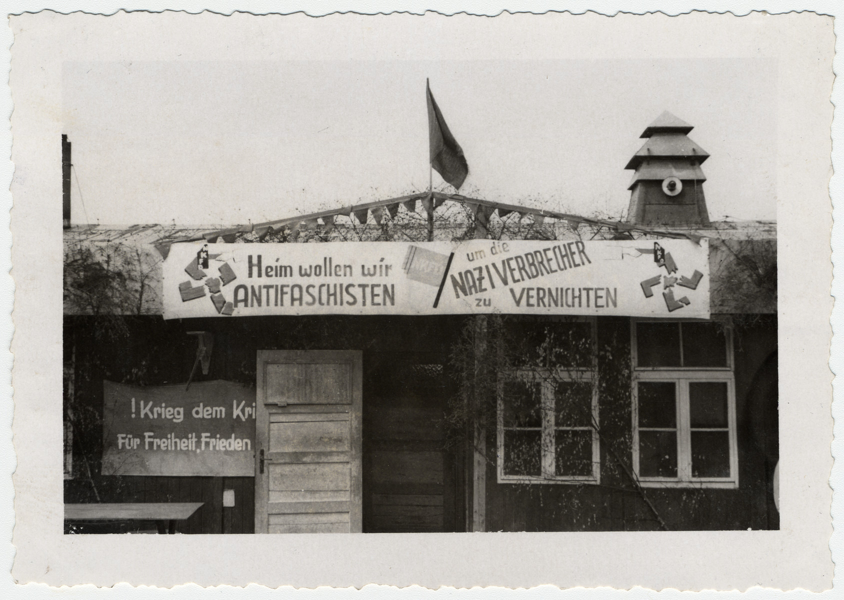 "Exterior view of a barrack in the newly liberated Buchenwald bedecked with an anti-Nazi sign.  It says, ""Heim wollen wir ANTIFASCHISTEN um die NAZI VERBRECHER zu VERNICHTEN,"" [At home we want antif-facists in order to kill the Nazi criminals]."