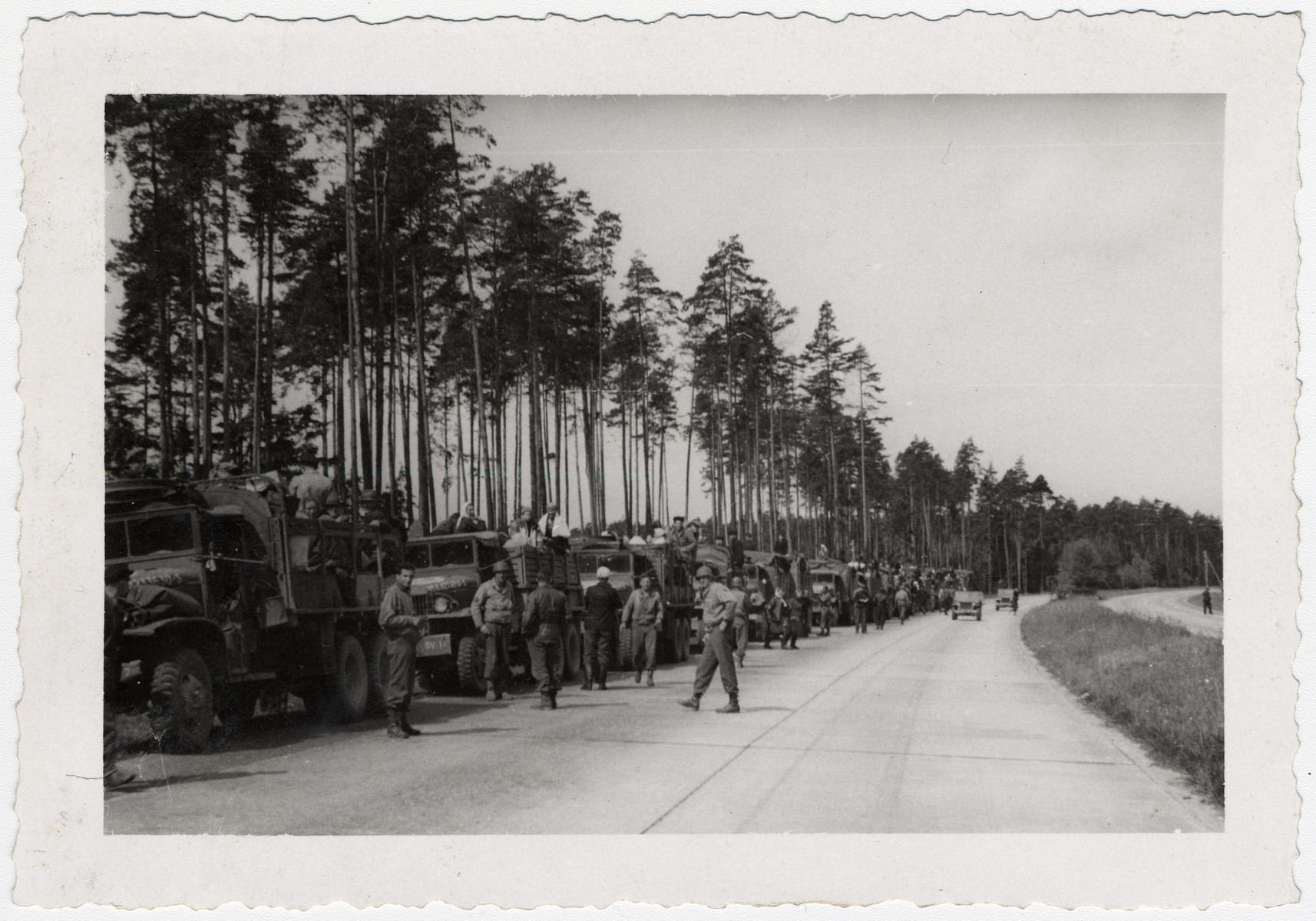 An American convoy leads survivors [probably of Buchenwald] out of the camp.