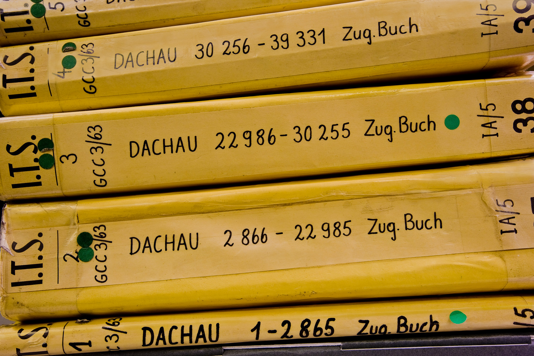 View of five I.T.S. Dachau records books stacked horizontally.
