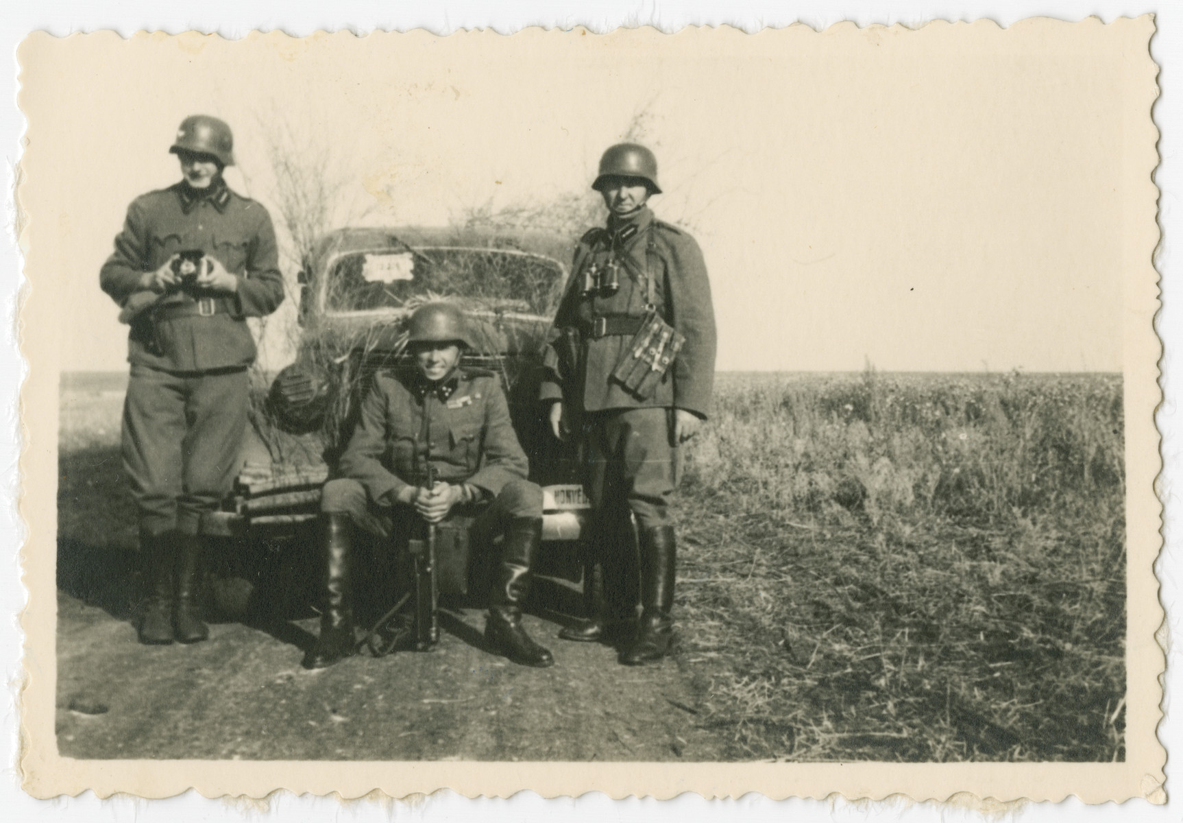 Karoly Deme, center, poses with two fellow soldiers before a camouflaged vehicle.