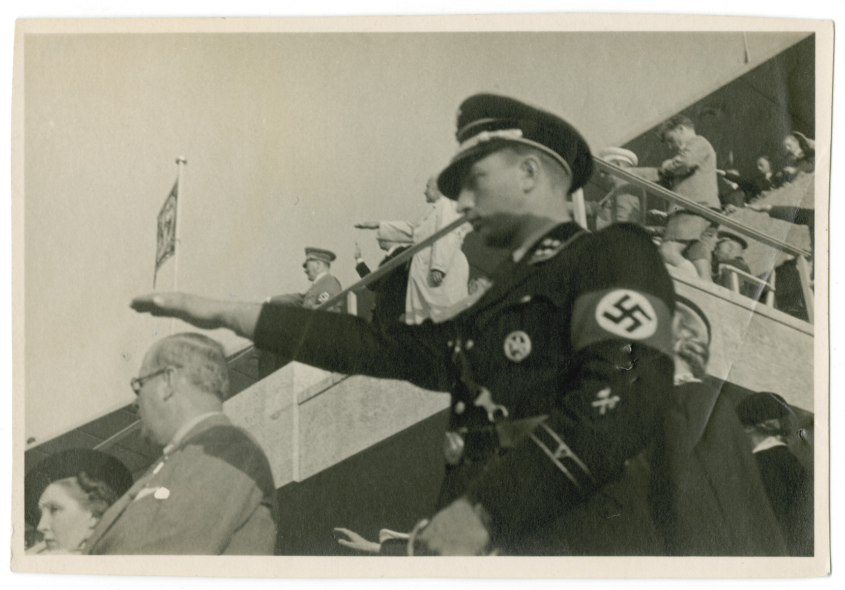 An SS man gives the Nazi salute at the start of the Berlin Olympics.  The saluting SS-man has been identified as SS-Sturmbannführer Hermnann Fegelein  The photograph was taken by Blanche Seimars (later Ensz) a young American woman visiting Germany from the United States.