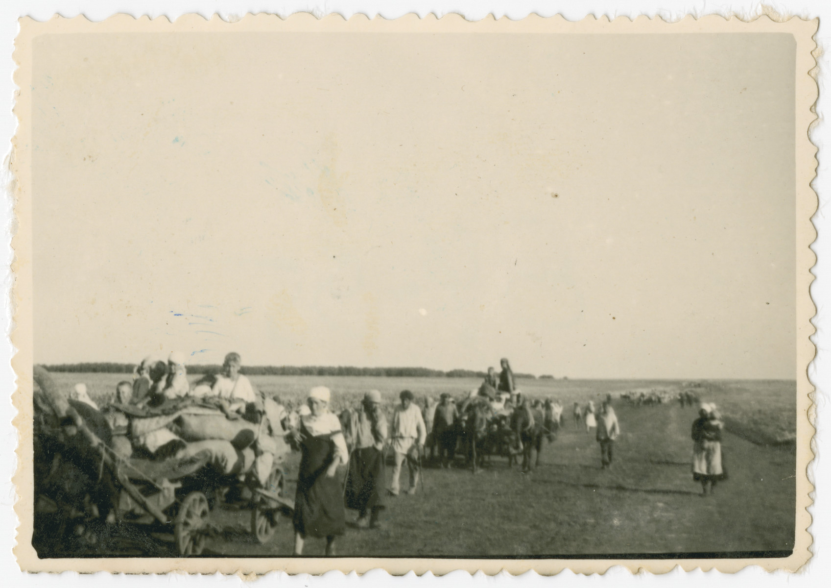 Photograph of civilians and wagons laden with  personal belongings taken during a possible resettlement action.