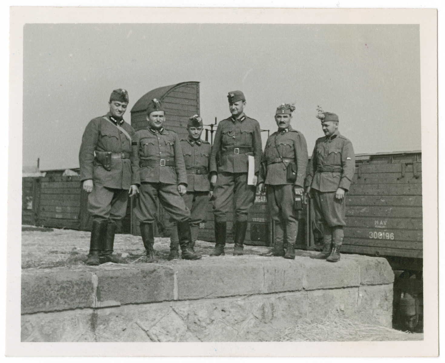Soldiers with the Hungarian Army's 20th Infantry Division pose before an unidentified railway.