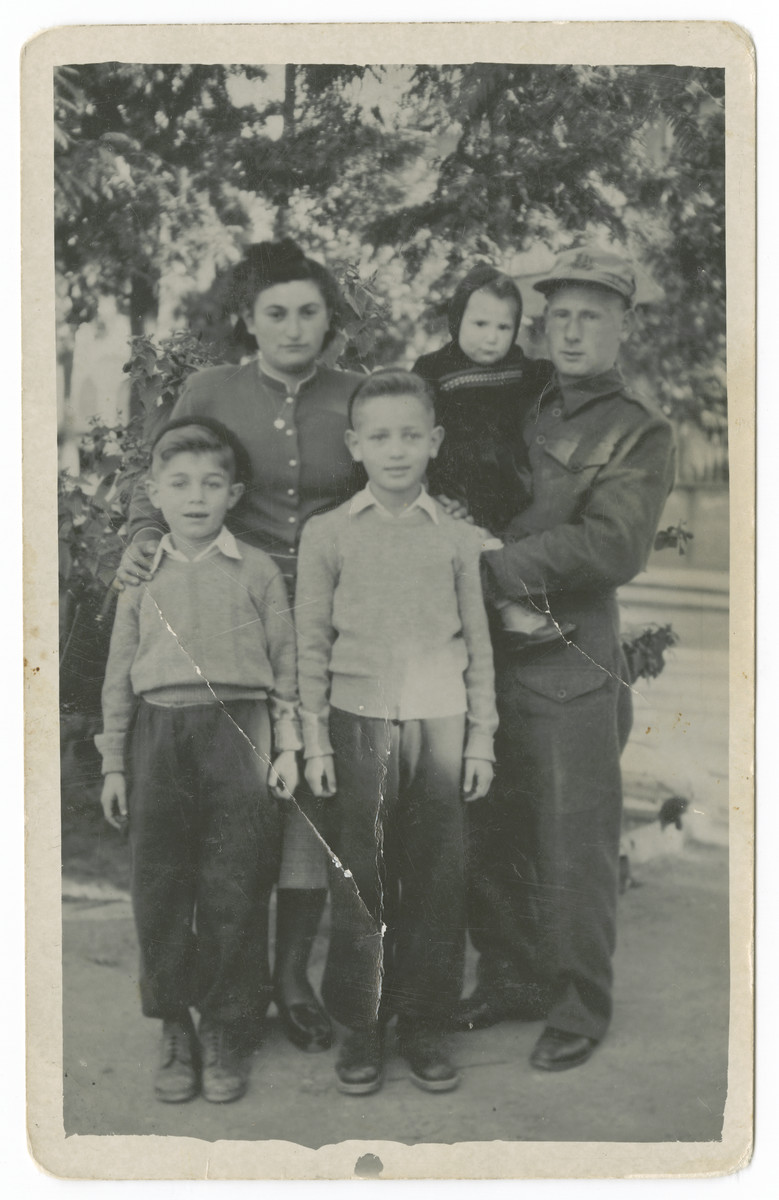 Postwar portrait of the Weinberg family.  Alter and Yitzchak Weinberg are in front. Behind them are their aunt and uncle Rivka and Hirsh Mayer Weinberg holding his daughter Tikva.