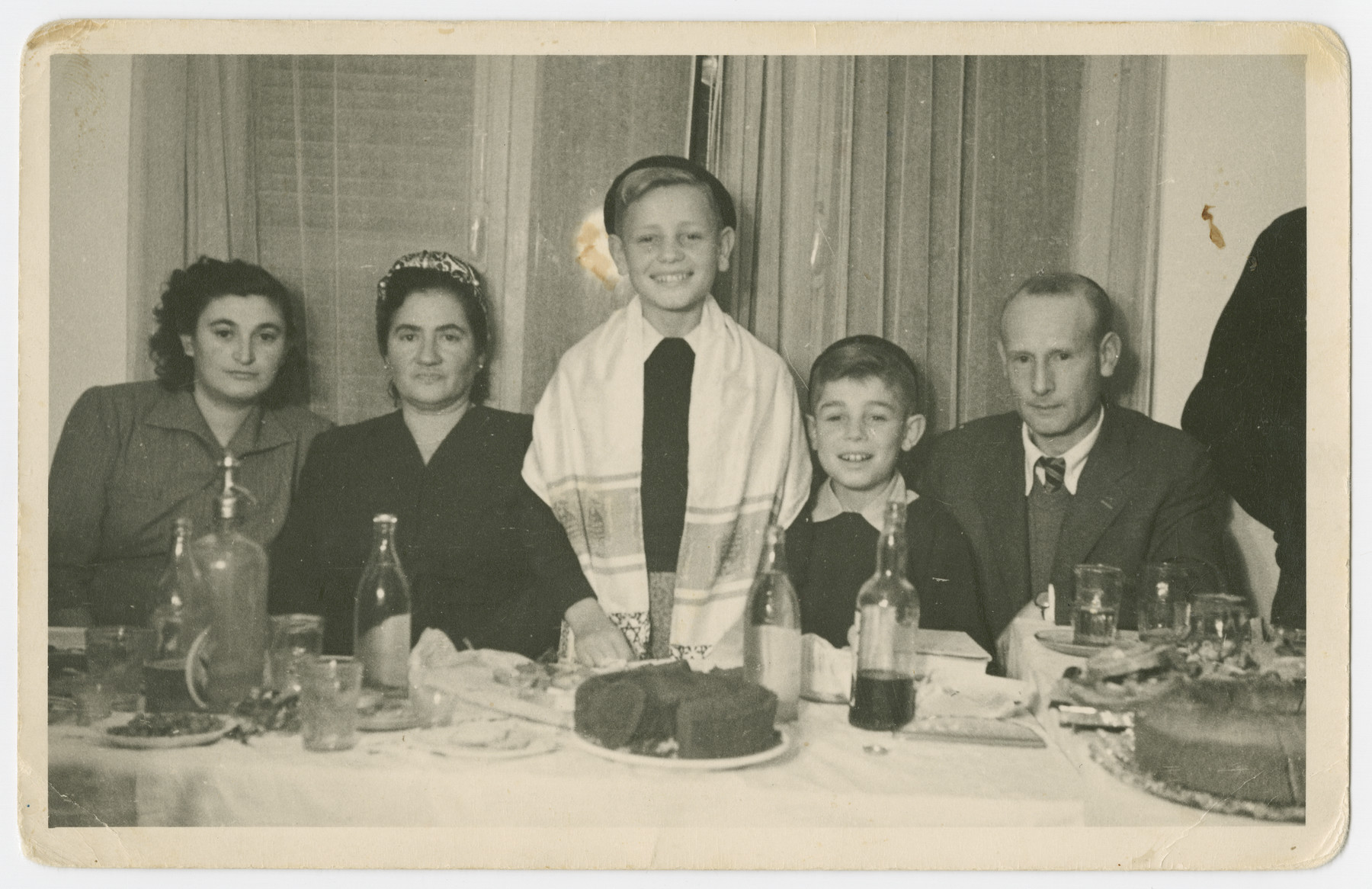 Yitzchak Weinberg celebrate his bar mitzvah with his relatives.  From left to right are Rivke Kupfer Weinberg, Ruche Wullinger (a greataunt), Yitzchak Weinberg, Alter Weinberg and Hircsh Mayer Weinberg. Yitzchak, Alter and Hirsch Mayer all escaped Poland through the Kalb rescue mission.