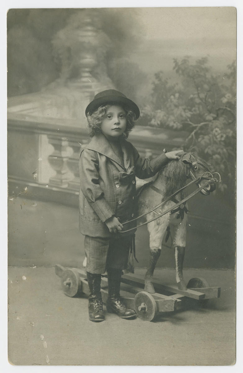Studio portrait of Mietek Juress as a young boy posing with a hobby horse.