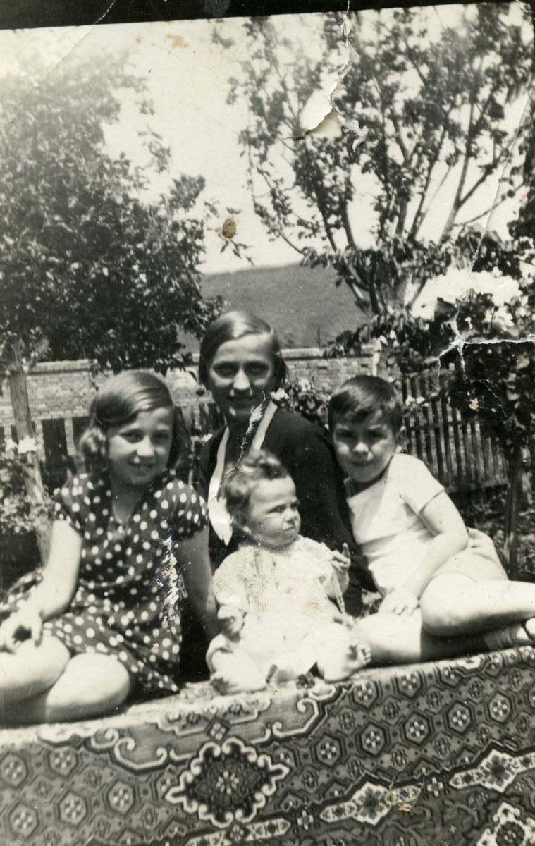 The Diamant children pose in a garden with their nanny.  Seated left ot right are Gertrude, Liane and Zigi.  Behind them is their governess Gretchen.