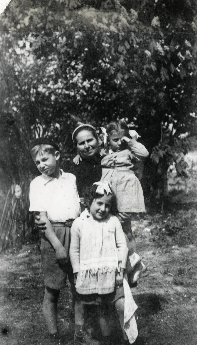"""Mrs. Josepovitz poses with three of the children in her charge in the Foublaines children's home.  Ewa Margules is in her harms and Jacob (her adopted brother) is by her side. The original inscription reads: For my dear parents Jacob""""."""