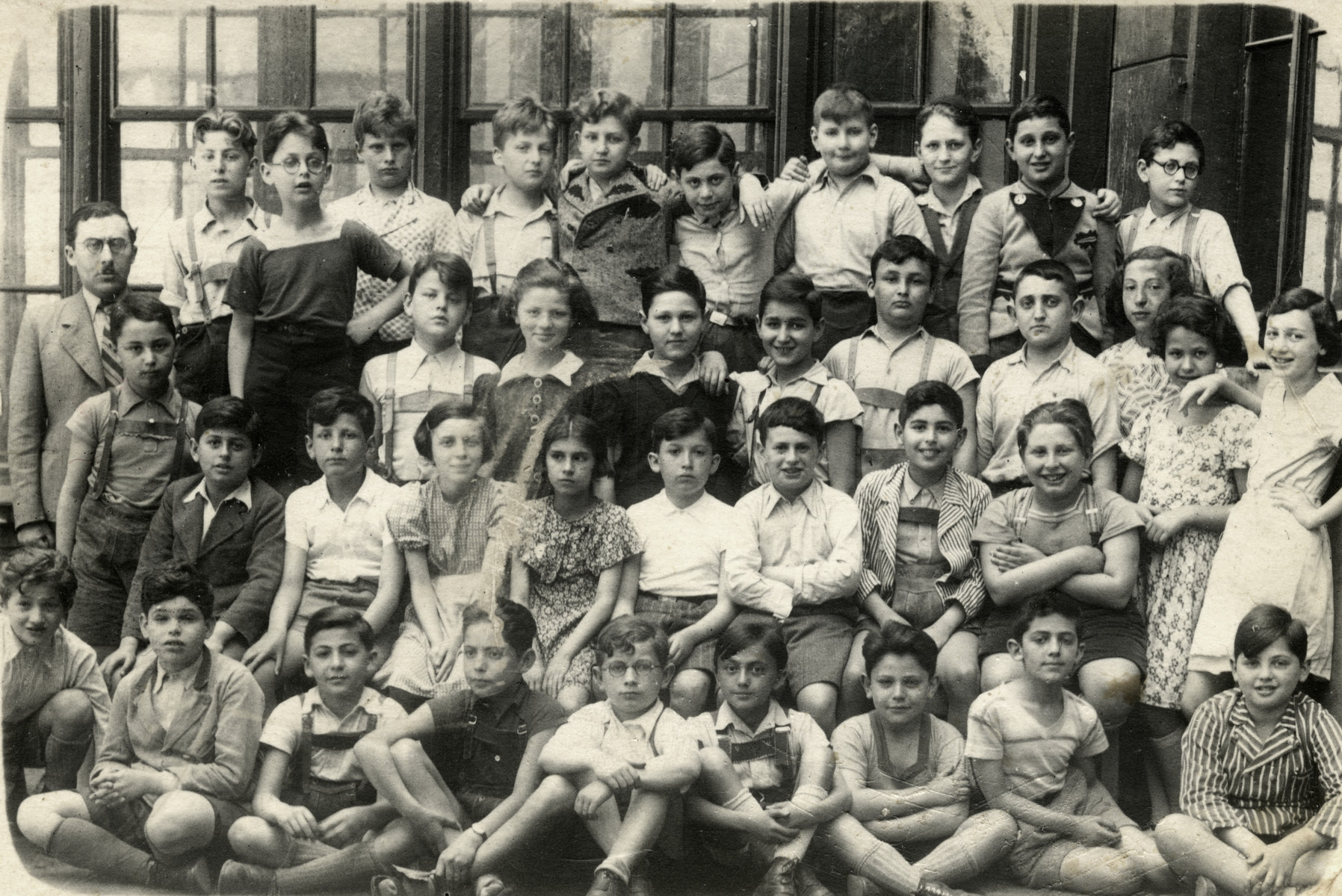 A group photograph of a class of the Chajes Realgymnasium in Vienna.   Gerda Beruh (age 10)  is standing on the far right in a white dress.